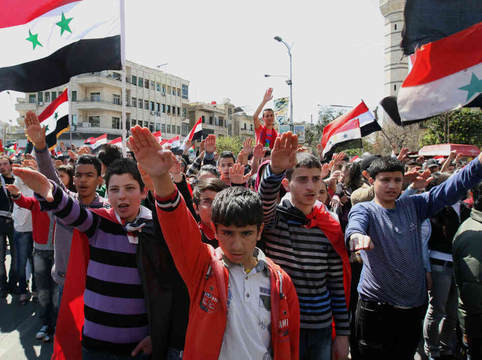 Syrian and Palestinian boys raise they hands and wave Syrian flags during a demonstration to mark Land Day in Damascus on March 30, 2012. Land Day, which began in 1976, marks the day Israeli forces killed six Palestinians during a protest against Israeli occupation of what Palestinians consider to be their land.