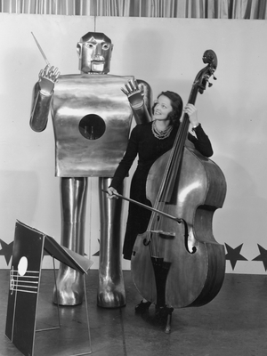 Musician Lois Kendall plays the bass while the robot Elektro