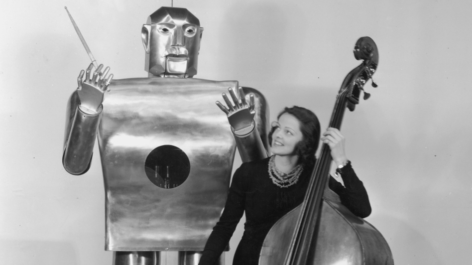 "Musician Lois Kendall plays the bass while the robot Elektro ""conducts"" on stage as part of a Westinghouse Electric and Manufacturing demonstration at the 1939 World's Fair in New York."