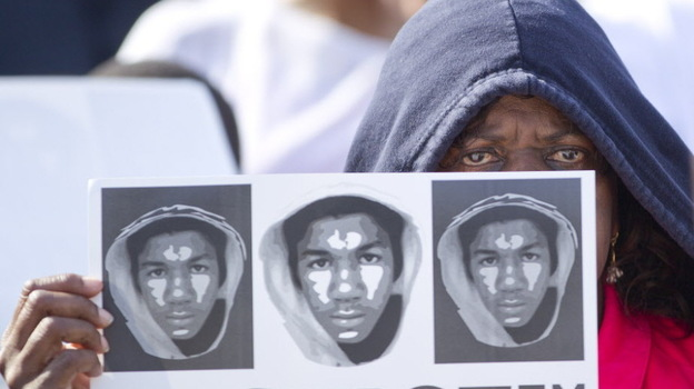 At a rally in Miami on Sunday, Arleen Poitier held a sign with images of Trayvon Martin.  (AP)