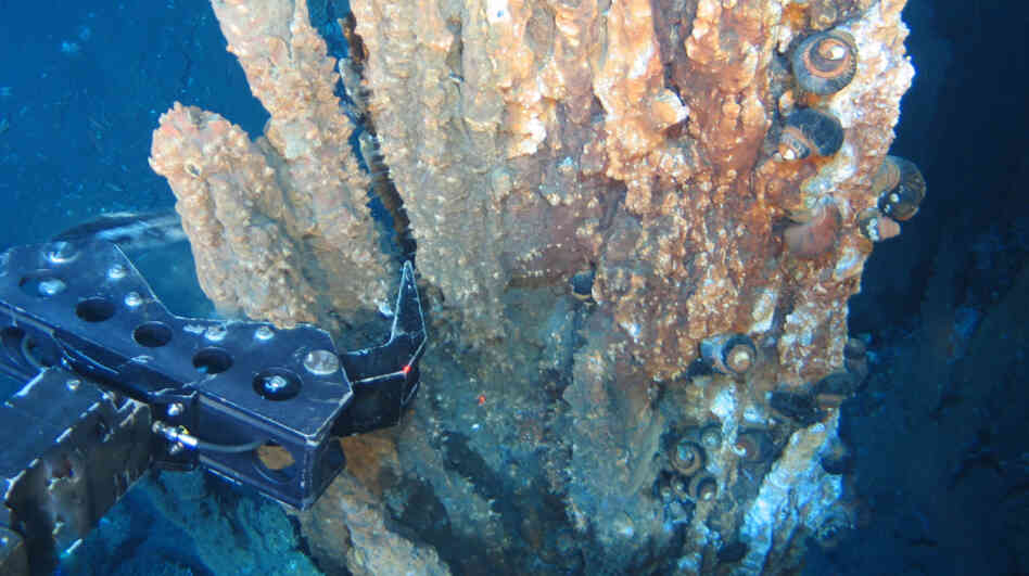 A robotic arm breaks off a chunk of mineral-rich rock deep underwater. Nautilus Minerals of Australia hopes to develop and expand undersea mining by extracting copper, gold, silver and zinc from the seafloor.