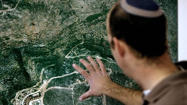 In this file photo, Israeli Amishai Shav-Tal, 31, one of the founders of the West Bank Jewish settlement of Bruchin, looks at an aerial photo of the settlement. (AP)