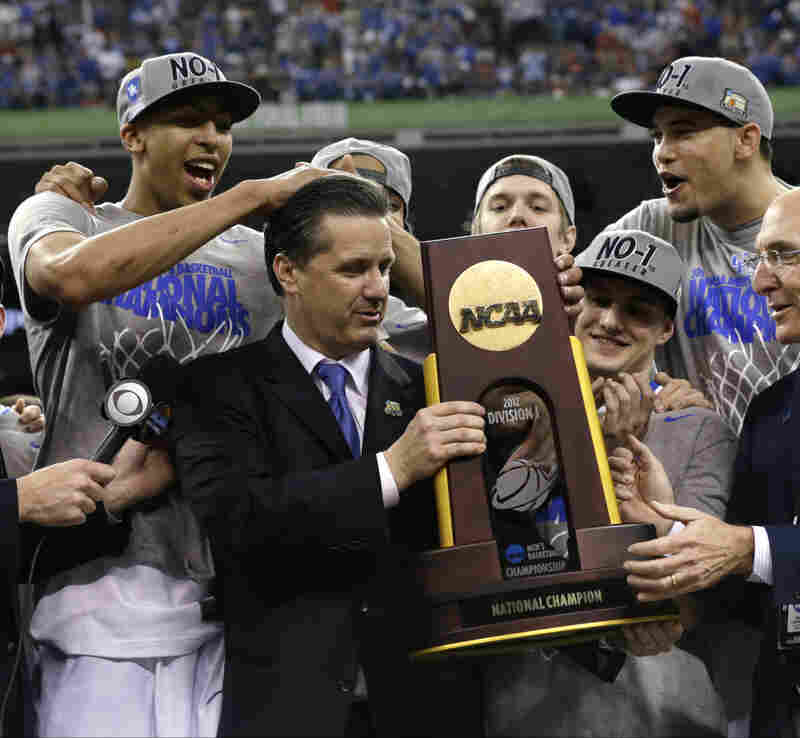 Kentucky head coach John Calipari (center) celebrates with his team after the Wildcats beat the University of Kansas on Monday to clinch the title.