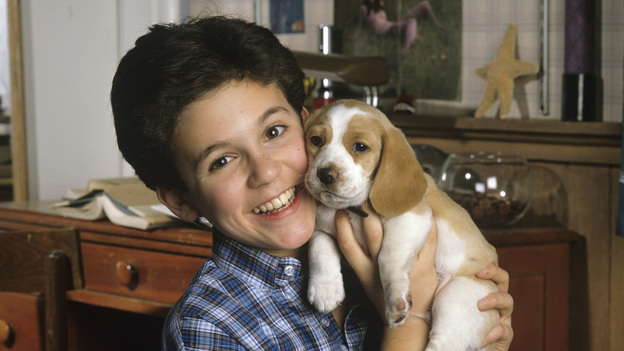 The face you may remember: Fred Savage cuddles up with a puppy on The Wonder Years, in a photo from December 1989. (Getty Images)
