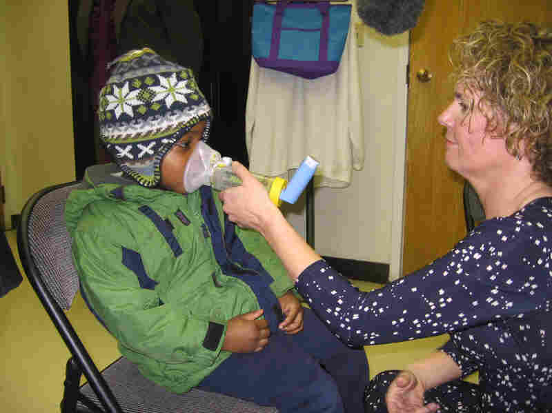 Kathy Harvey of the Zigler Head Start Center in New Haven, Conn., gives 4-year-old student Anthony Hebert an asthma treatment.