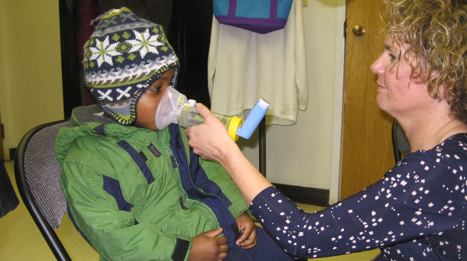 Kathy Harvey of the Zigler Head Start Center in New Haven, Conn., gives 4-year-old student Anthony Hebert an asthma treatment. (NPR)