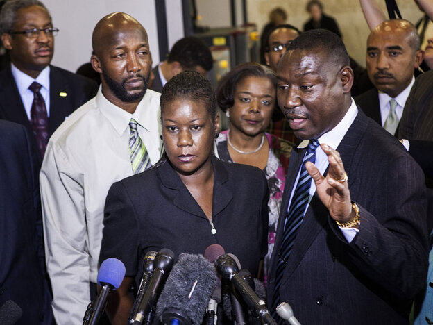 Sybrina Fulton (C) and Tracy Martin (L), parents of Trayvon Martin, listen while their friend and lawyer Benjamin Crump speaks to the