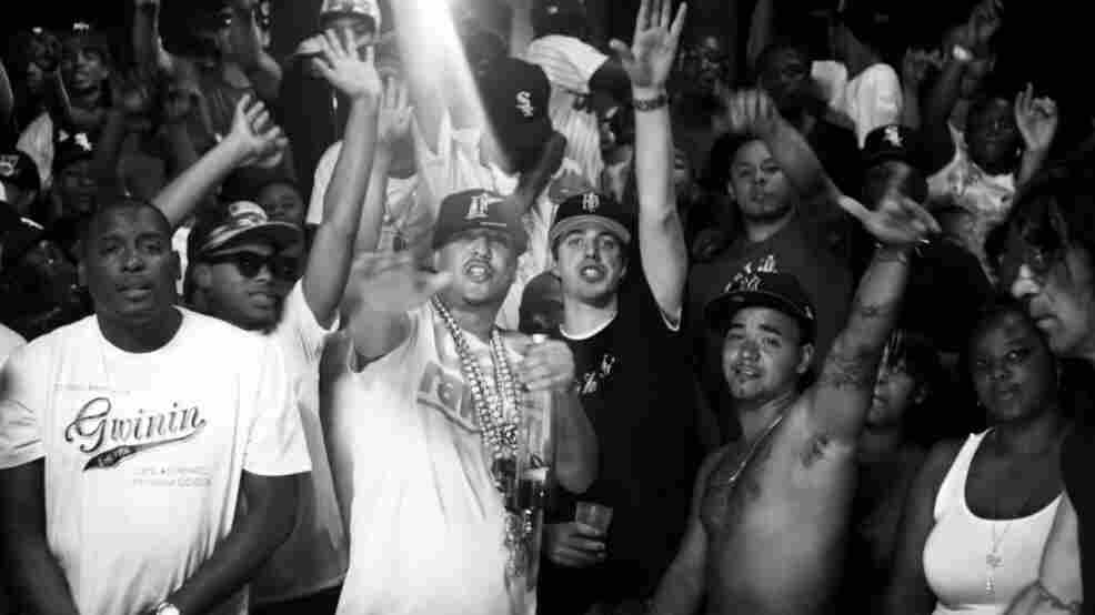 """French Montana (in white shirt, chains and hat) and Harry Fraud (black shirt, black hat) at the center of the video for Montana's song """"Shot Caller,"""" which Fraud produced."""
