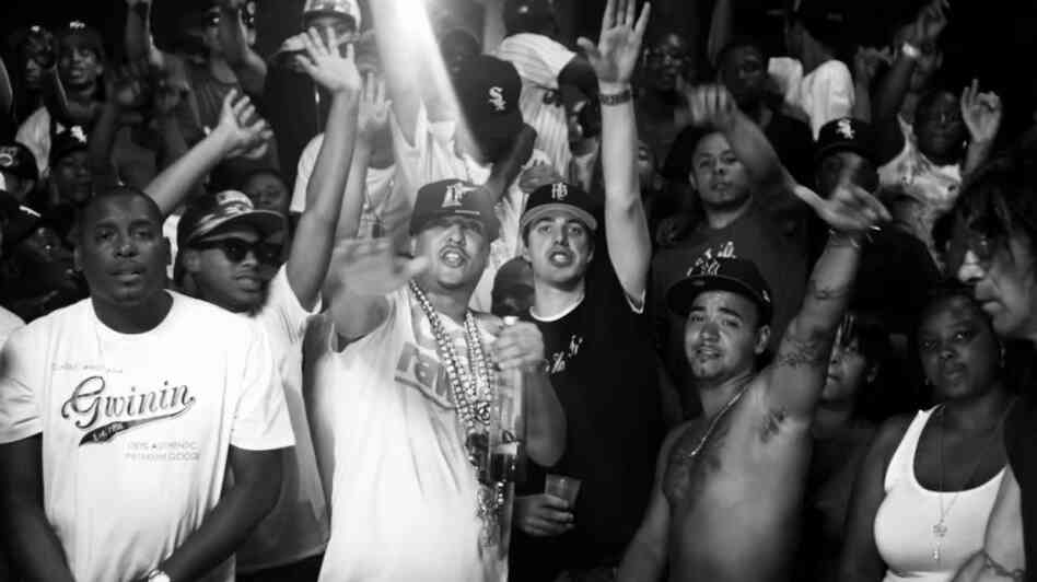 "French Montana (in white shirt, chains and hat) and Harry Fraud (black shirt, black hat) at the center of the video for Montana's song ""Shot Caller,"" which Fraud produced."