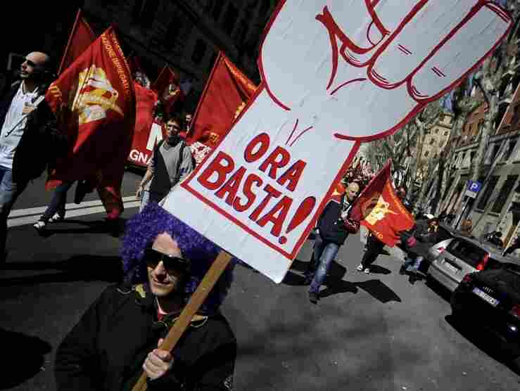 "Members of the Italian metalworkers trade union Fiom-CGIL hold a placard reading ""Enough now!"" during a protest in Rome on March 9."