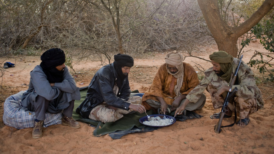 Tuareg rebels eat a meal last month near the Malian city of Timbuktu, which they recently captured. The rebels have taken control of northern Mali, raising concerns about stability in the broader region.  (Ferhat Bouda/DPA/Landov)