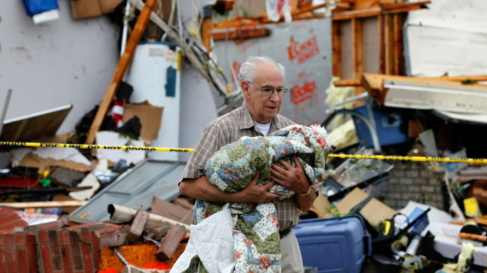 In Arlington, Texas, Tuesday afternoon, David Lowe carried his daughter's dog, Phoebe, away from the rubble.  (Getty Images)