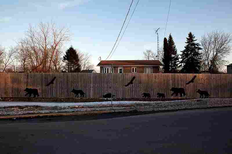 The three spirit animals — the bear, the eagle and the wolf — adorn a fence in Kahnawake.