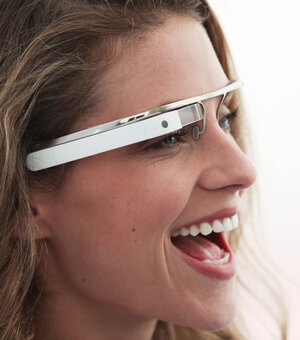 A woman wears a design version of Google's intended smart glasses from its Project Glass.