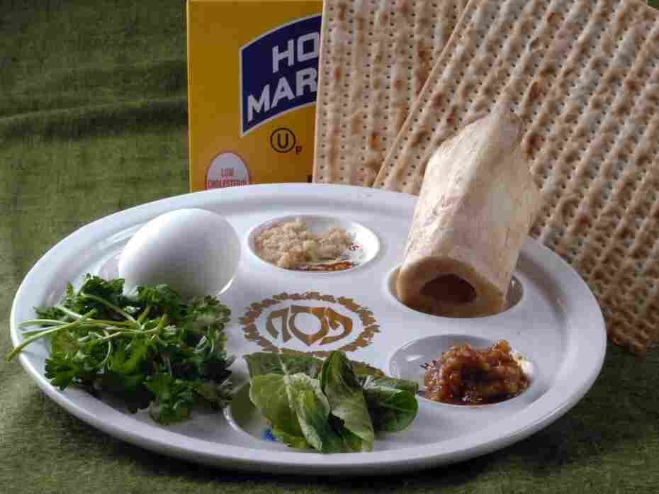 The Passover Seder plate with symbolic foods (clockwise, from top center): horseradish; a shank bone; a mixture of fruit, wine and nuts called haroset; lettuce, parsley and an egg.