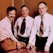 Intel's first hire (from left), Andy Grove, and Intel co-founders Robert Noyce and Gordon Moore in 1978, the 10th anniversary of the company. Grove is sitting on a graphical layout (a rubylith) of one of Intel's early microprocessors.