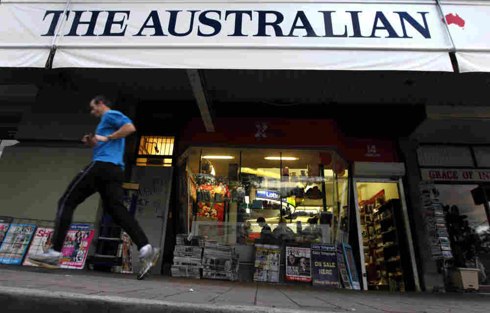 A jogger runs past a banner for The Australian, part of Rupert Murdoch's newspaper empire, in Sydney last year.