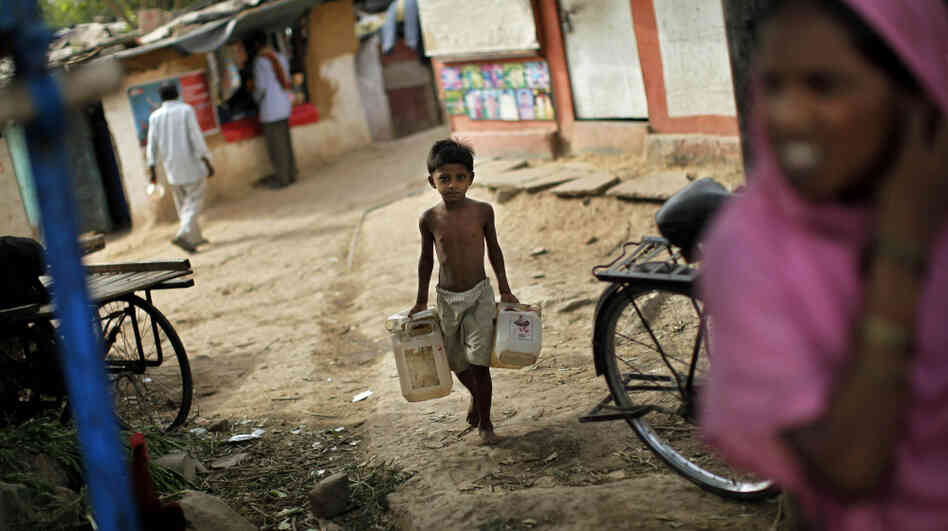 An Indian boy carries empty canisters to be filled at a water depot in a New Delhi slum. Data from India's latest census shows that although millions of Indians have access to technology such as TVs and cellphones, many millions more still lack basic amenities such as sanitation and w