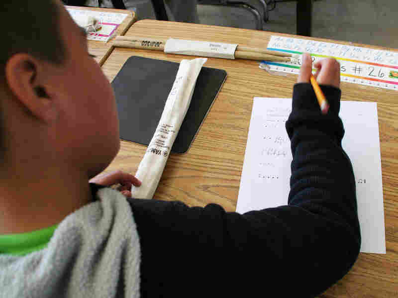 A student at Allen Elementary fills out a worksheet where music notes are converted into fractions.