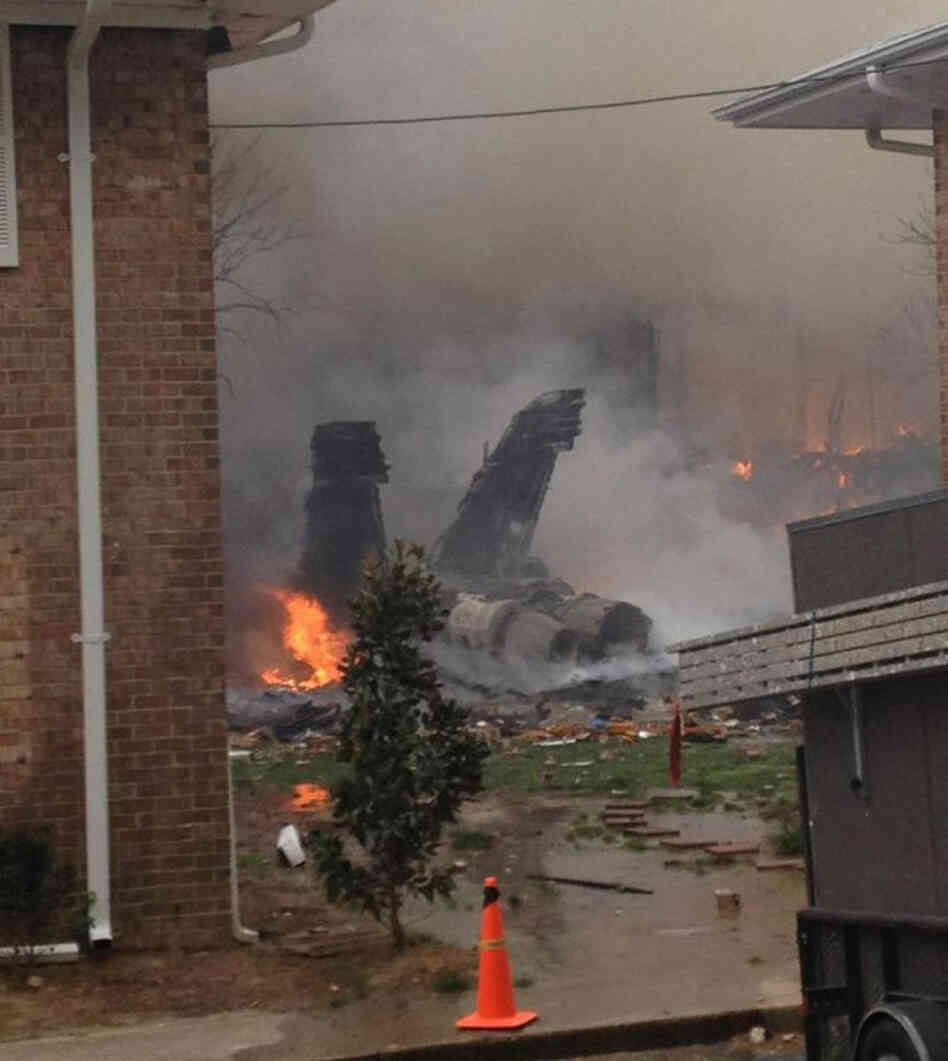 The burning fuselage of an F/A-18 Hornet lies smoldering after crashing into a residential building in Virginia Beach, Va. on Friday.