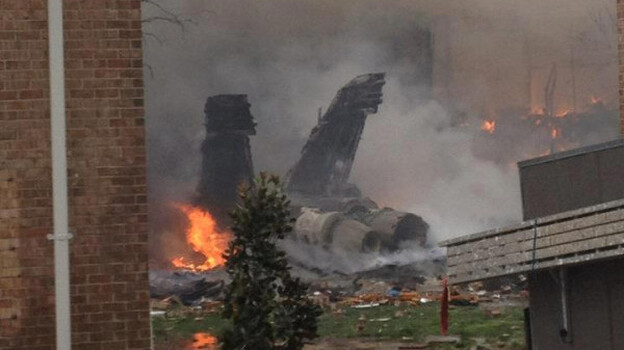 The burning fuselage of an F/A-18 Hornet lies smoldering after crashing into a residential building in Virginia Beach, Va. on Friday. (AP)
