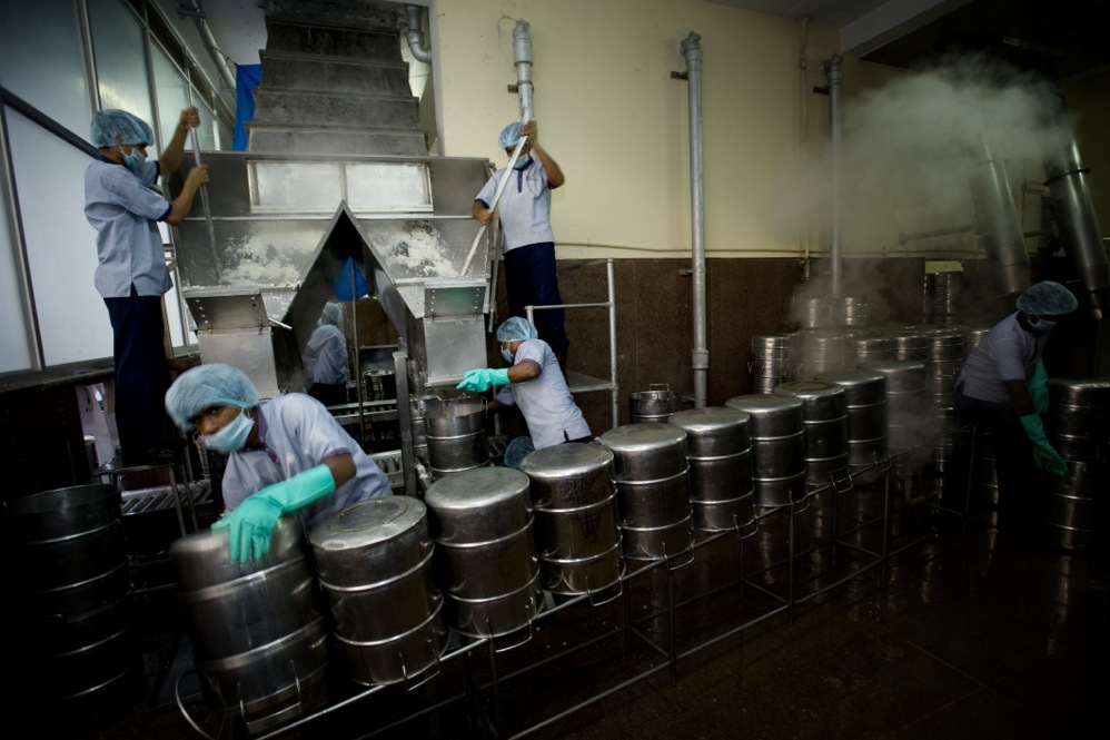 Rice falls down a chute (top left) and is packed into sterilized stainless steel vessels for delivery to schools. Over time, Akshaya Patra has learned what children like in different regions and has customized the kitchen according to the local palate.