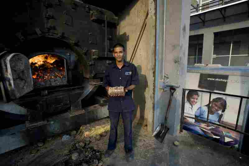 A workman holds a fuel briquette made from sugarcane waste, seed waste and peanuts. The briquette powers the kitchen's boilers.