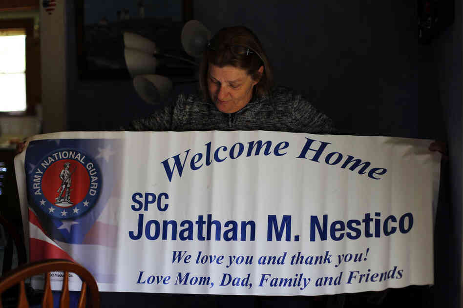 Judy holds up a welcome home banner from John's last noncombat deployment.