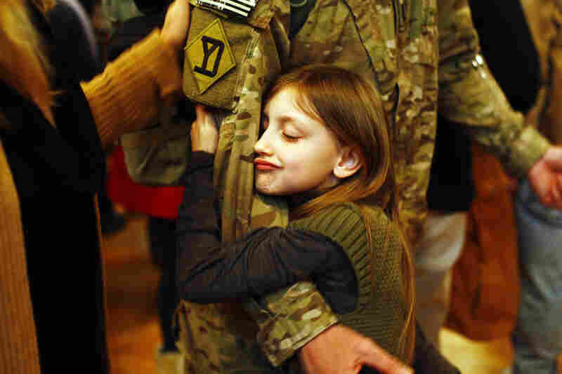 Gracelyn Currie, 7, hugs her father, Michael, at the conclusion of the welcome home ceremony.