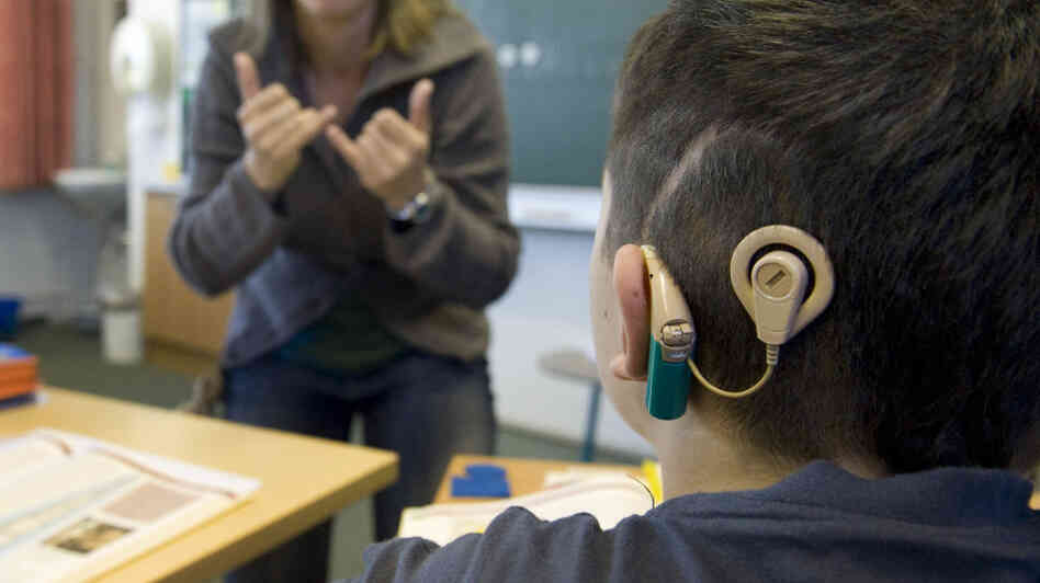 A schoolboy with a cochlear implant listens to his teacher during lessons at a school for the hearing impaired in Germany. The implants have dramatically changed the way deaf children learn and transition out of schools for the deaf and into classrooms with non-disabled students.