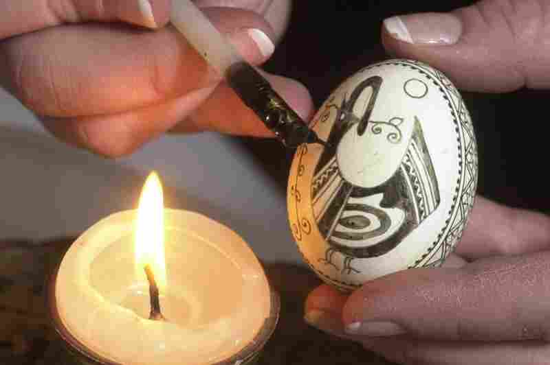 An artist uses a stylus to decorate an egg with melted wax, the traditional Ukrainian technique for crafting pysanka.