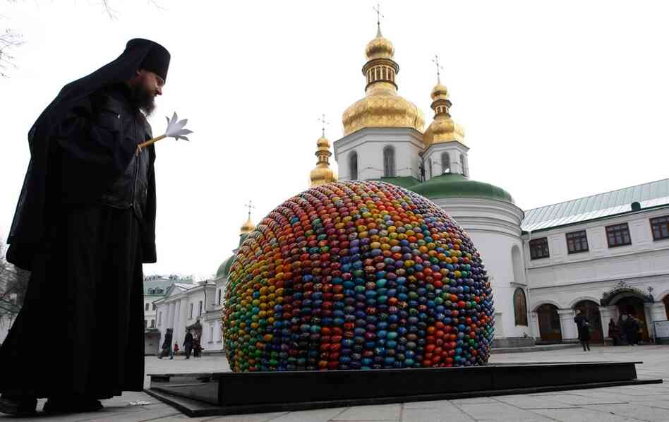 A priest peers at an egg sculpture built of 3,000 wooden eggs outside a cathedral in Kiev.