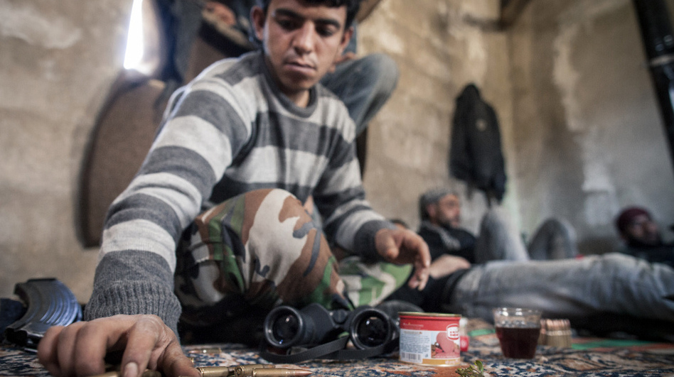 A Syrian soldier who defected and joined the Free Syrian Army sits at an outpost near the village of Janudieh. Some defectors say the military is committing atrocities, but that the rebels are fighting back with their own brutality.
