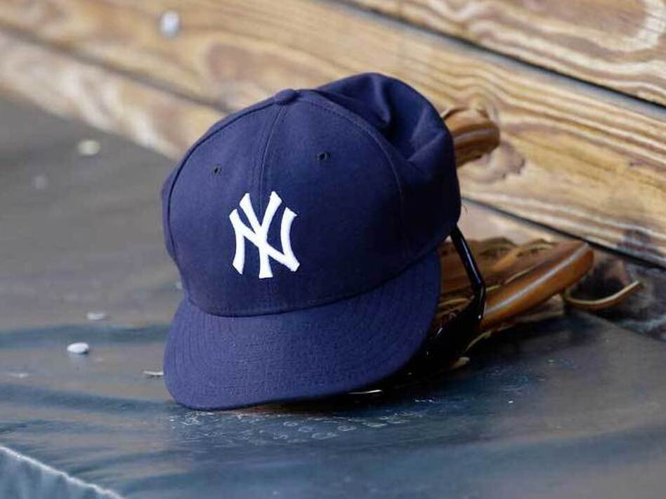 A New York Yankees hat and glove rest in the dugout before a game at Oriole 750b785d9a2b