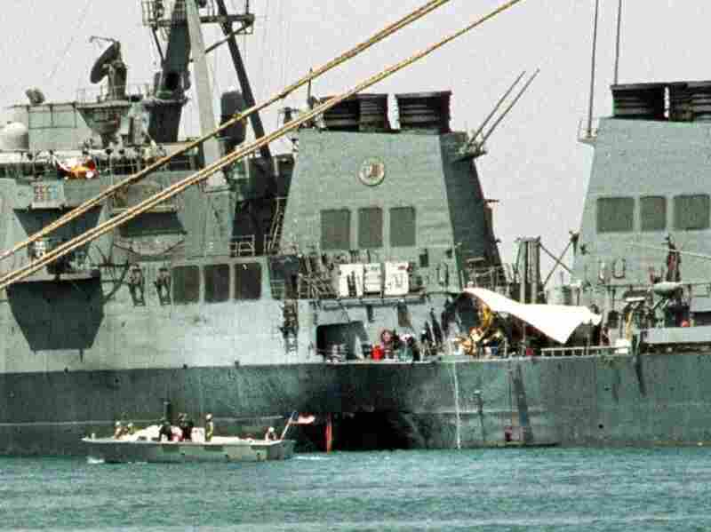 A small boat guards the USS Cole in Aden, Yemen, on Oct. 20, 2000. Abd al-Rahim al-Nashiri, the man accused of masterminding the attack, is expected to testify Wednesday in a courtroom at Guantanamo Bay.