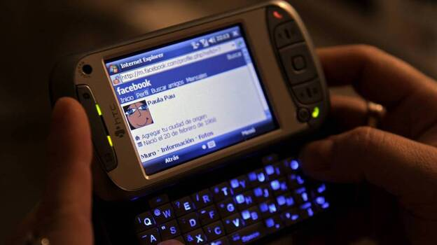 A woman uses her smartphone to access Facebook. Several states are close to banning employers from asking job applicants for their social media login information. (AFP/Getty Images)