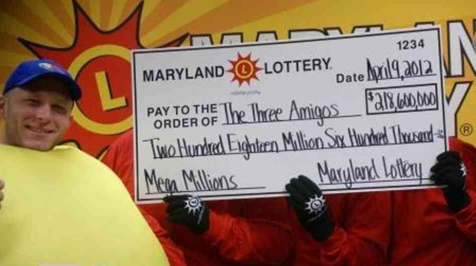 The three anonymous Mega Millions winners celebrate their $218.6 jackpot with a lotto friend.
