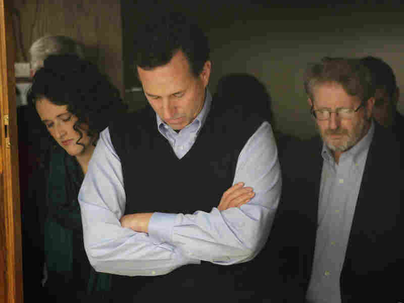 Santorum bows his head in prayer during a campaign rally in the basement of the Northwestern Bank building in Orange City, Iowa, on Jan. 1.