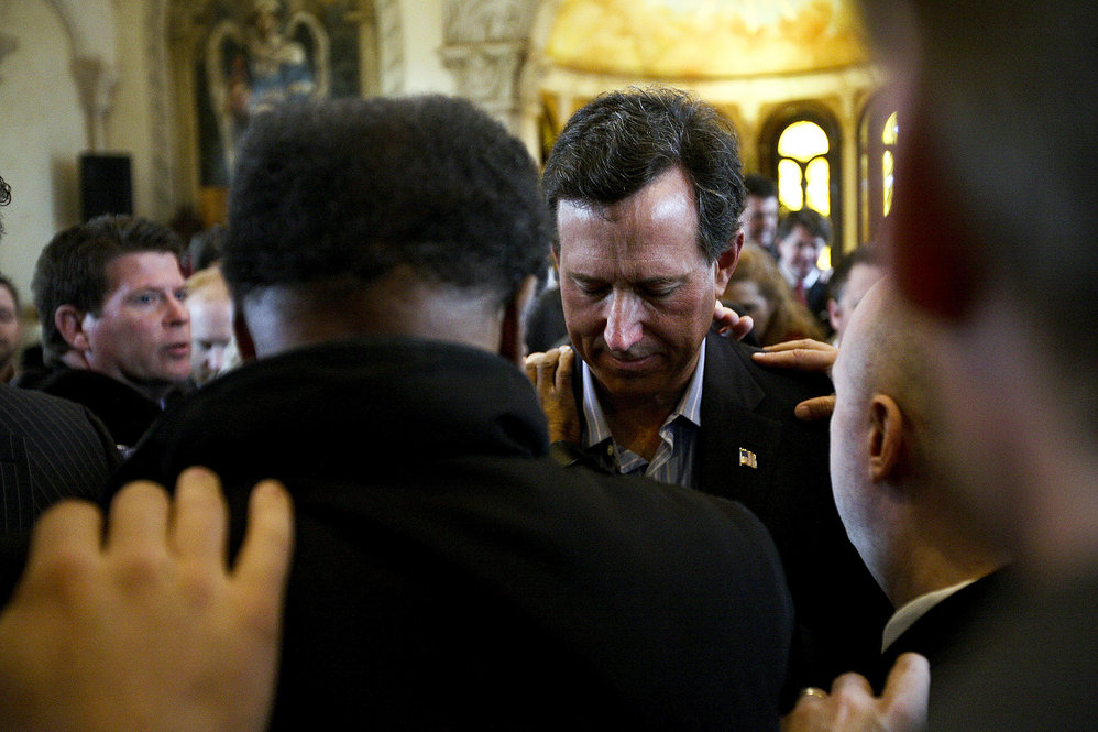 A day after Santorum's Feb. 7 victories in Colorado, Minnesota and Missouri, supporters in McKinney, Texas, pray over him.