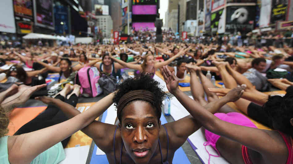 Bernice Acosta and other yoga enthusiasts practice in New York's Times Square at an event marking the 2011 summer solstice. Some Hindus say such events have little to do with yoga's s