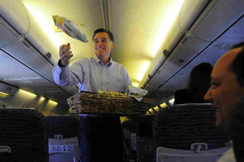 Peanuts! Popcorn!: Mitt Romney throws snacks to journalists on his campaign plane in Jacksonville, Fla., in January.
