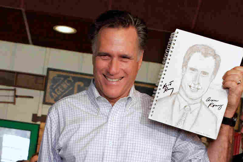 Spittin' Image: Romney holds up a sketch drawn by a supporter during a campaign stop in Rockford, Ill., in March.