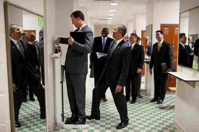 Tripped Up: Obama puts his toe on the scale as Trip Director Marvin Nicholson weighs himself at a University of Texas locker room in 2010.