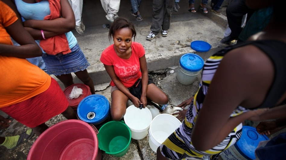 Marlene Lucien controls the hose that fills people's plastic buckets on one busy street corner in Port-au-Prince, Haiti. (NPR)