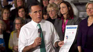 "Mitt Romney holds a flier titled ""Women & The Obama Economy"" as he speaks in Hartford, Conn., Wednesday"