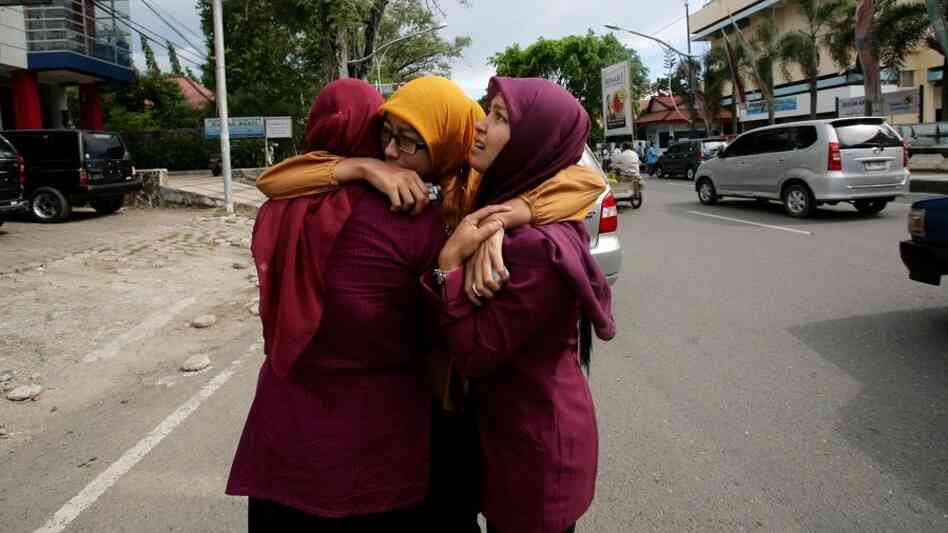 Acehnese women hug each other shortly after the powerful  earthquake hit the western coast of Sumatra in Banda Aceh.