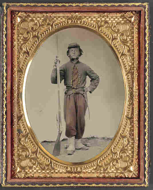 A tintype photograph shows an unidentified Union soldier at the time of the Civil War, standing with his bayoneted musket.