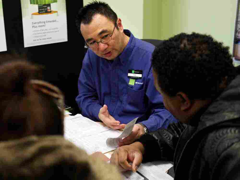 In this Friday, Jan. 6, 2012 photo, Tai Sung, a master tax advisor for H&R Block, center, consults with clients about their taxes at his office in Rockville, Md. In our second hour, listeners talk about the lessons they've learned over years of filing.
