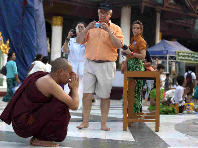 Foreign tourists photograph a monk praying at the Shwedagon Pagoda in Yangon, Myanmar.