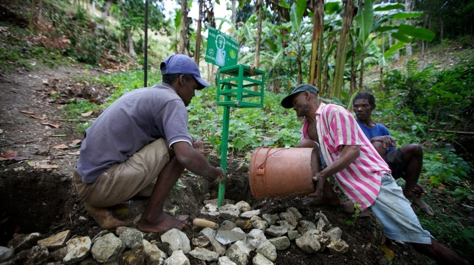 "Men in the hillside village of Font de Liane in Haiti install a ""chlorine box,"" a dispenser that adds just the right amount of chlorine to disinfect a five-gallon bucket of water. Cholera bacteria infect many streams in Haiti that people use for drinking, bathing and washing clothes.   (NPR)"